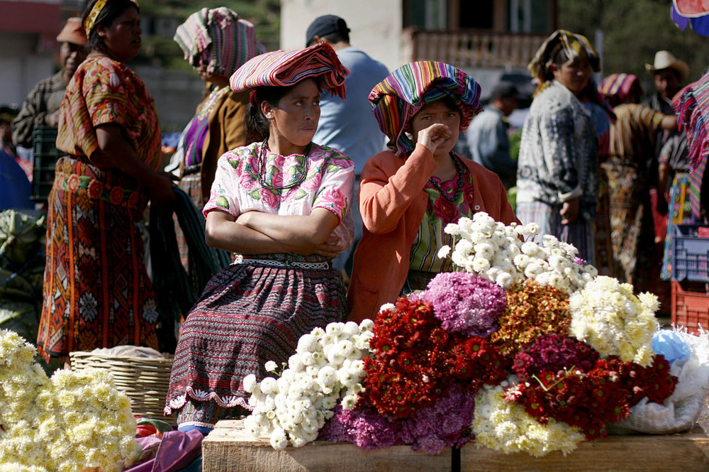 Women sell flowers in an outdoor market in Zunil, a small town near Quetzaltenango, Guatemala. At the market an announcer advertised items over a loudspeaker as farmers hurried around the square carrying huge bushels of vegetables.