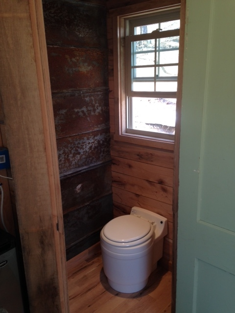The tin wall to the left will eventually have a door to an outside shower. Since the toilet is not permanently in place, it can be moved against the other wall.