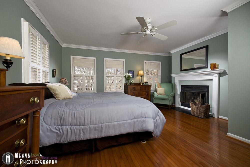 Master bedroom using light painting techniques to highlight fireplace, molding, hardwood floors - creating a welcoming warm atmosphere to the room.