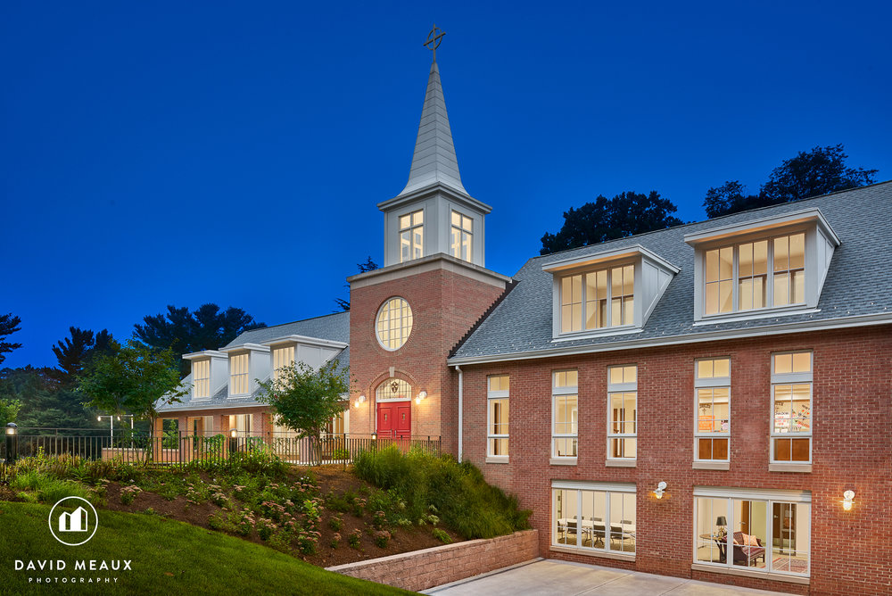 Twilight photo highlighting the two-story tall Parish Hall with classroom on bottom floor and tower with steeple above.