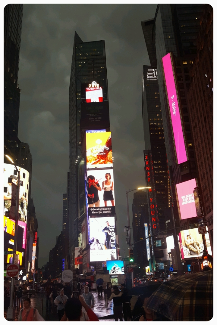 Times Square on a cloudy night after a massive rain storm.
