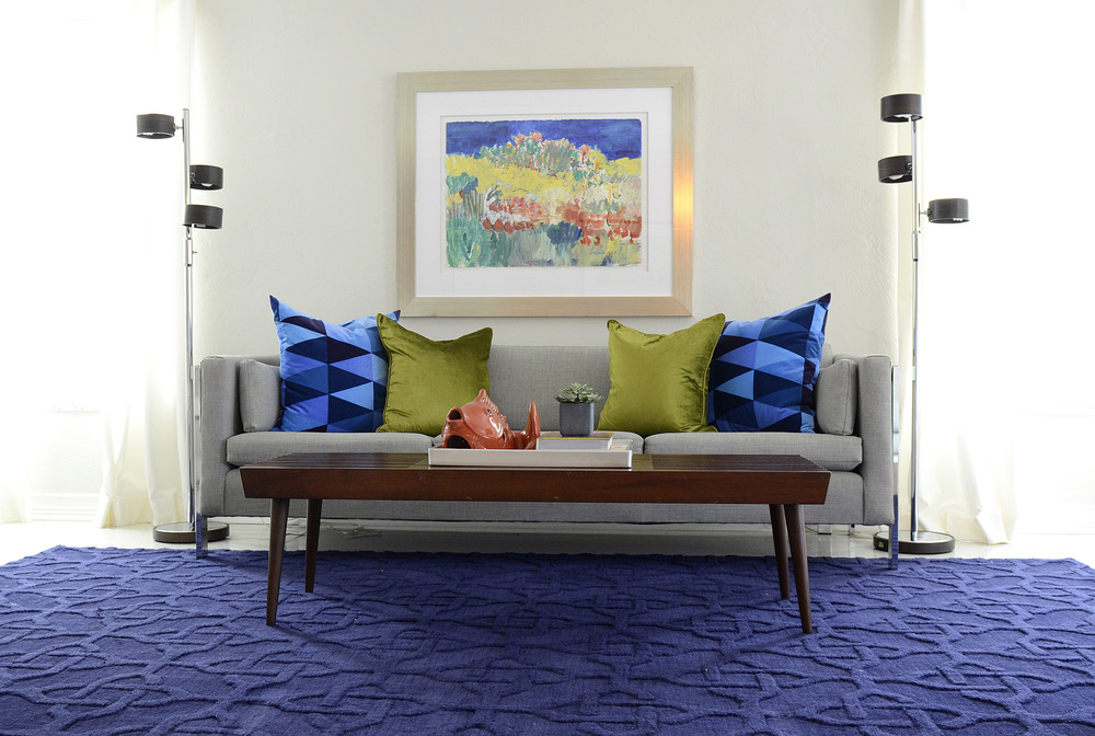 Image Credit In our client's mid century inspired home we popped up the crisp space with rich blues through art and textiles. We love how the blue rug looks against the sleek terrazzo floors.