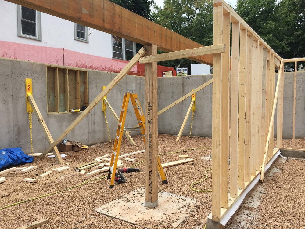 Photo taken Friday, 1:20 p.m., looking southwest from a future office to a future bedroom (the framed-in wall opening can be a double window opening into an area well).  The stair up will rise between the column and stud wall.