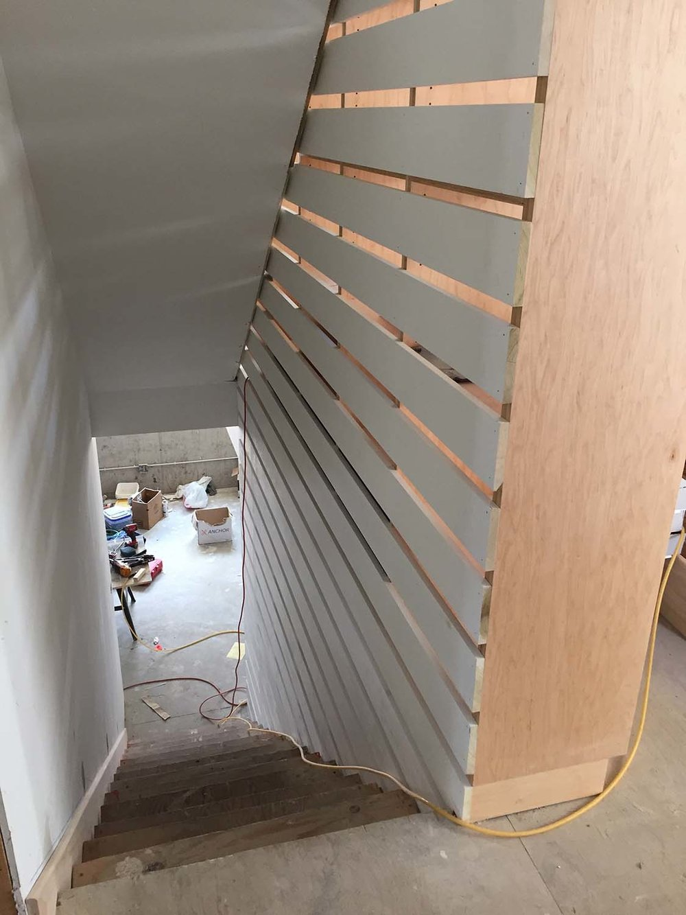 This image shows the slats alongside the stairwell.  They are continuous from the basement through the top level, providing the code-mandated barrier while allowing peek-a-boo glimpses through it.