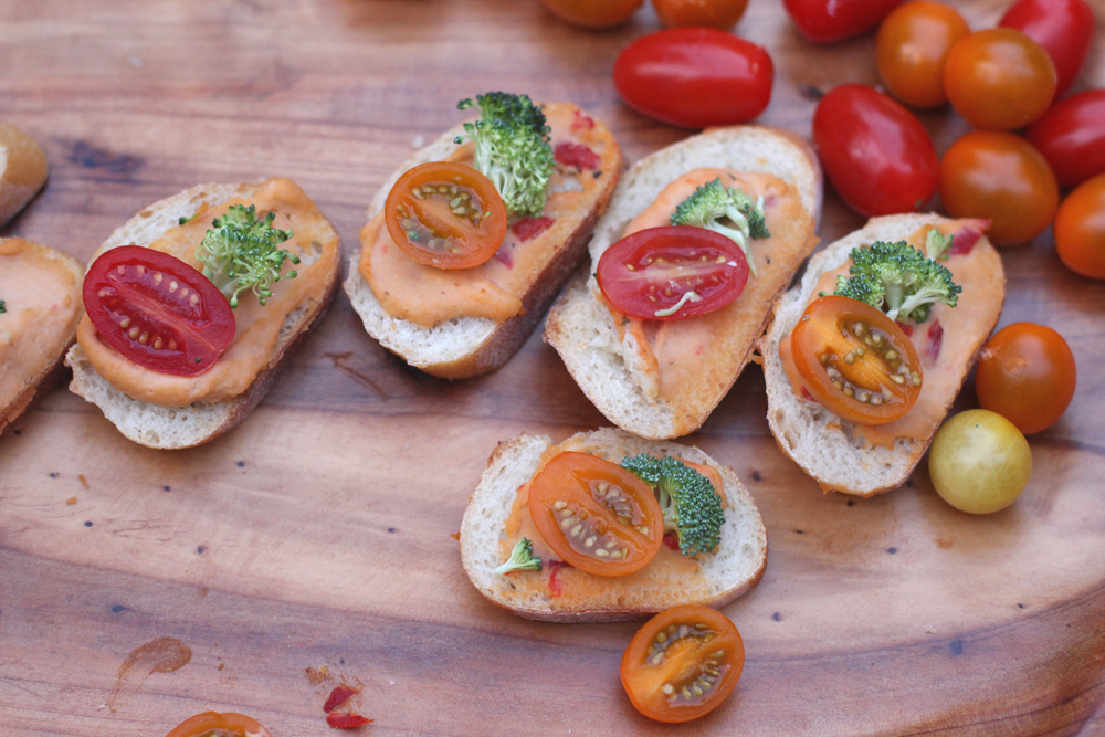 Roasted red pepper hummus crostini with cherry tomatoes & broccoli