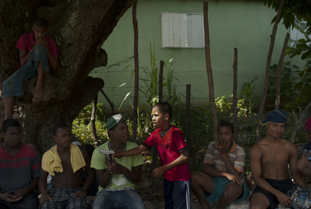 Kids play with a toy gun,  Paraiso, Dominican Republic.