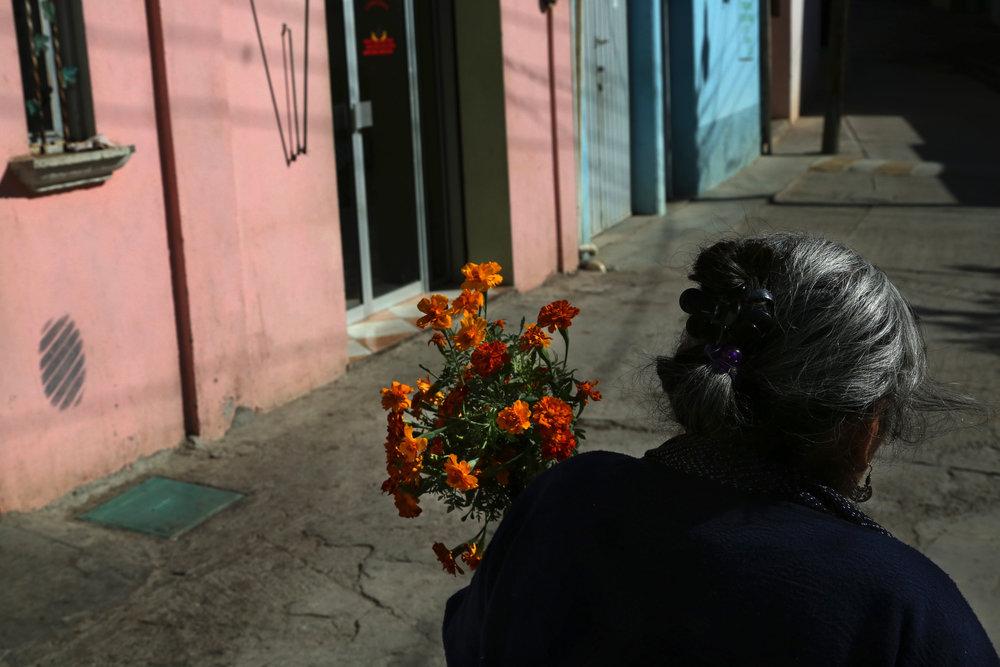 Teresa Raymundo carries flowers to a funeral in  San Juan del Rio, Oaxaca.