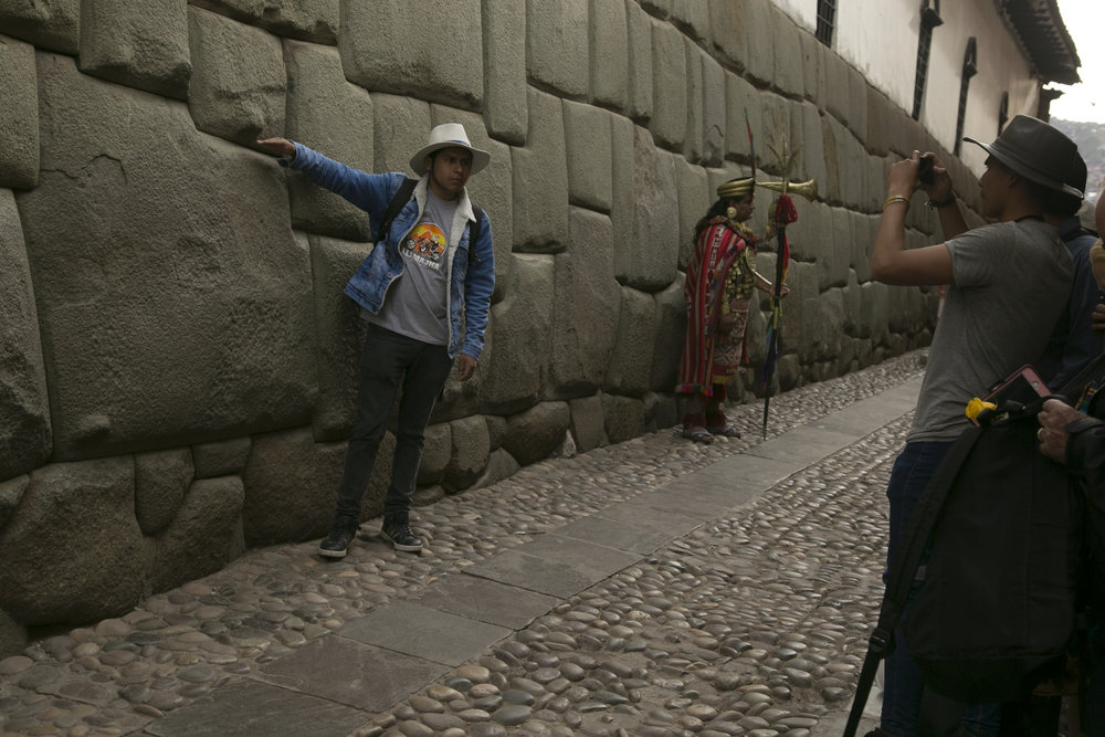 A tourist takes a picture with the famously intricate twelve-angled stone that's part of an Incan foundation in Cusco, Peru.