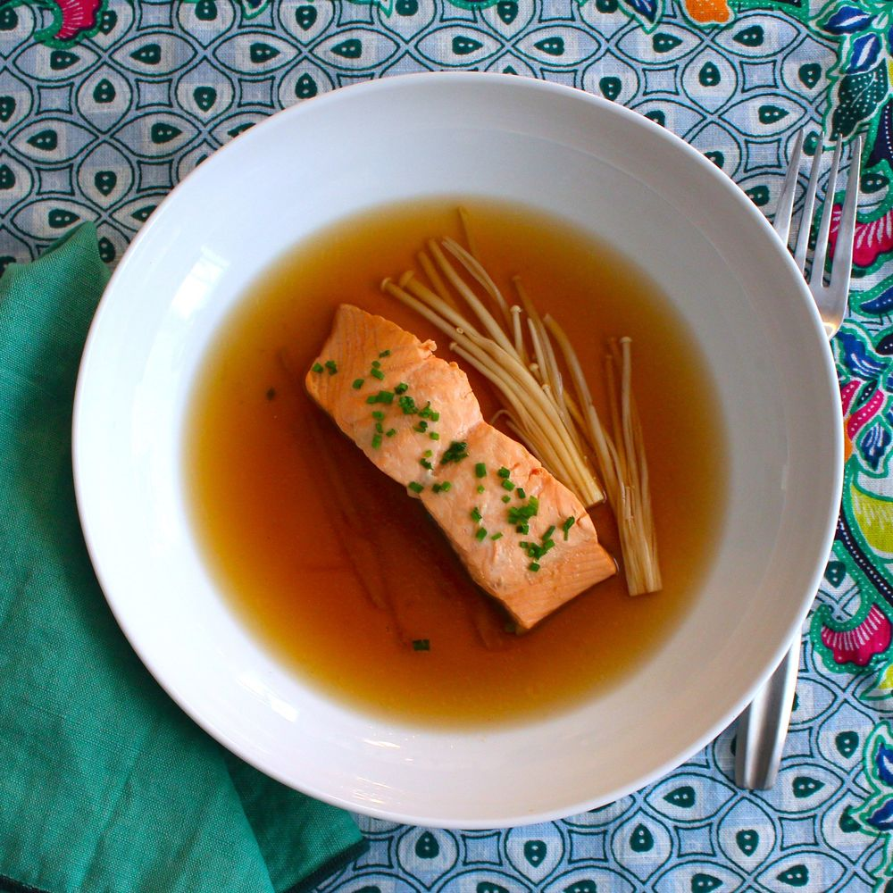 Salmon is poached with dashi, mirin and soy sauce with enoki mushrooms