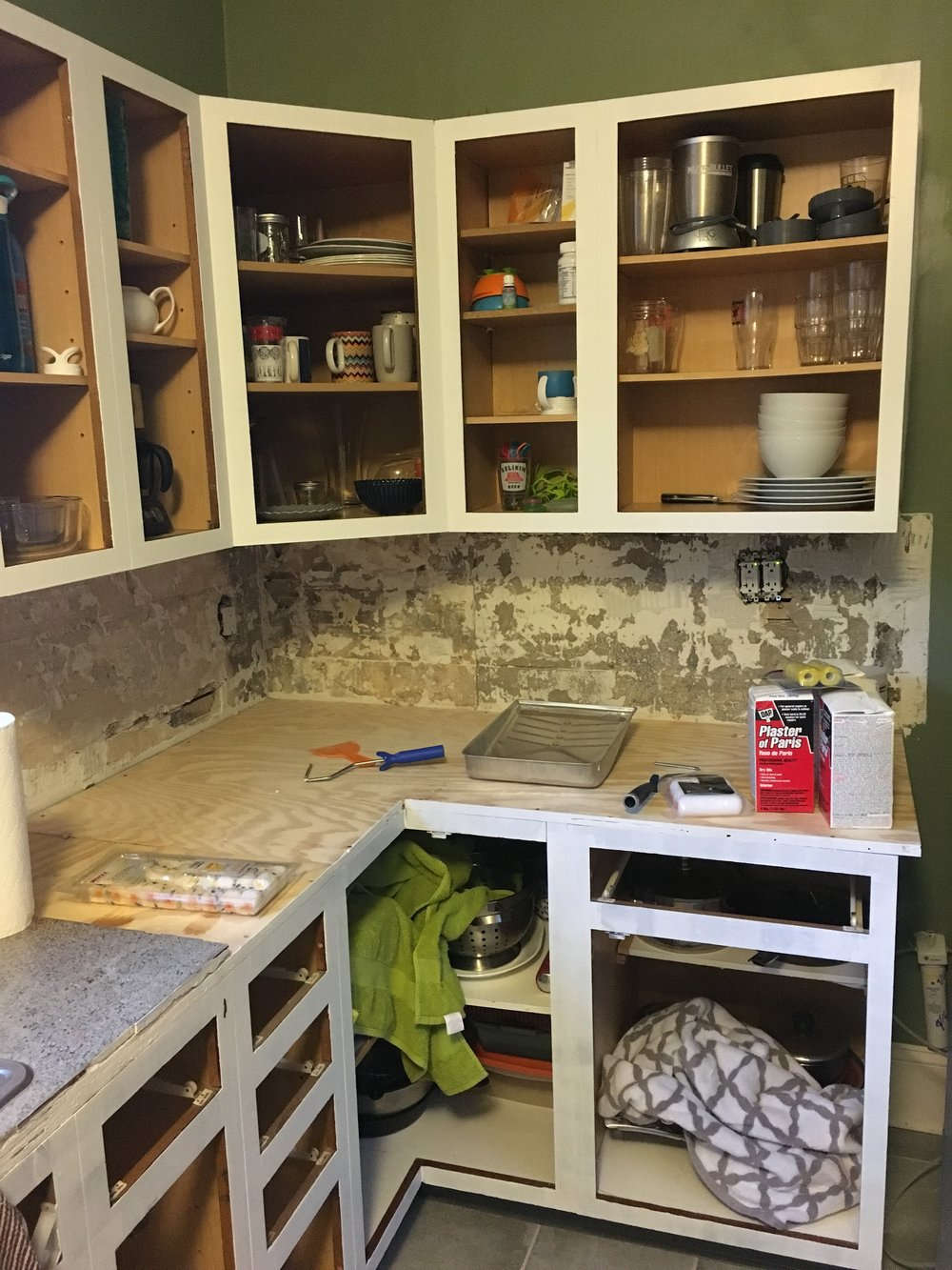 A coat of paint on the cabinet bases and Plaster of Paris for wall patching. A half-hearted attempt to protect the dishes with towels.