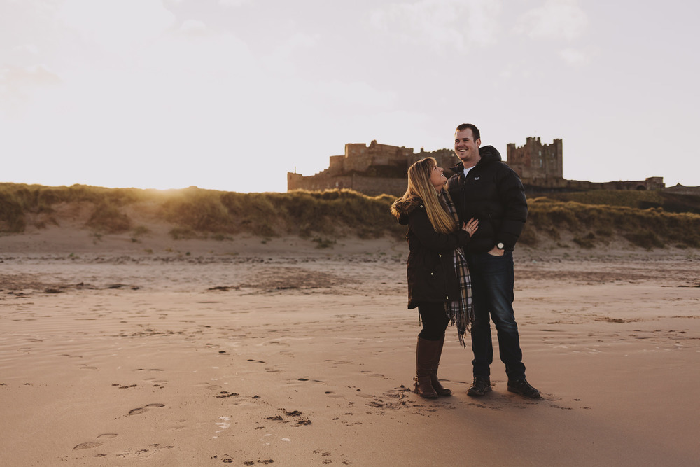 Callum and Dannielle on Bamburgh Beach, Northumberland Coast, with Bamburgh Castle behind them