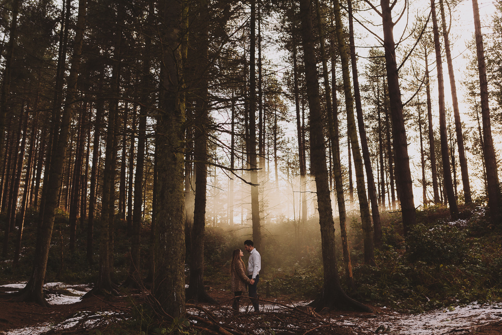 Engaged couple holding hands in an old wood in Newcastle upon Tyne with mist hanging in the air