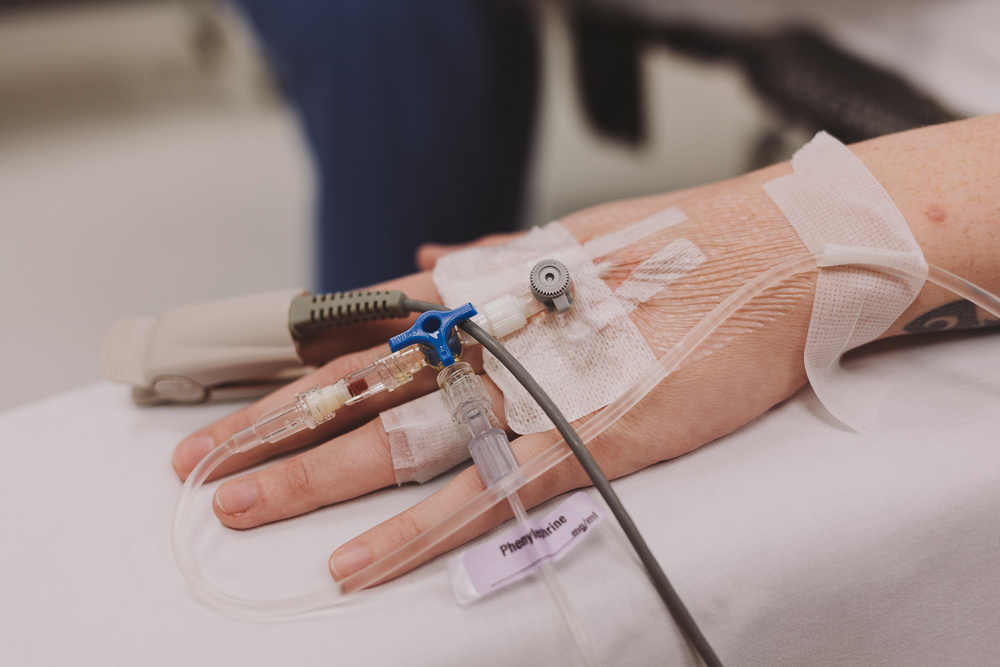 Close up on Alicia's hand, hooked up to a heart monitor and with a canula