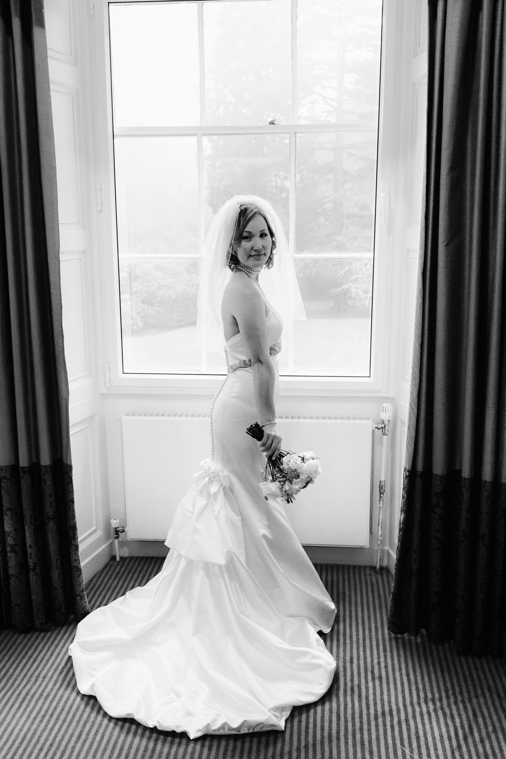 Black and white portrait of the bride in front of a window at Linden Hall, Northumberland
