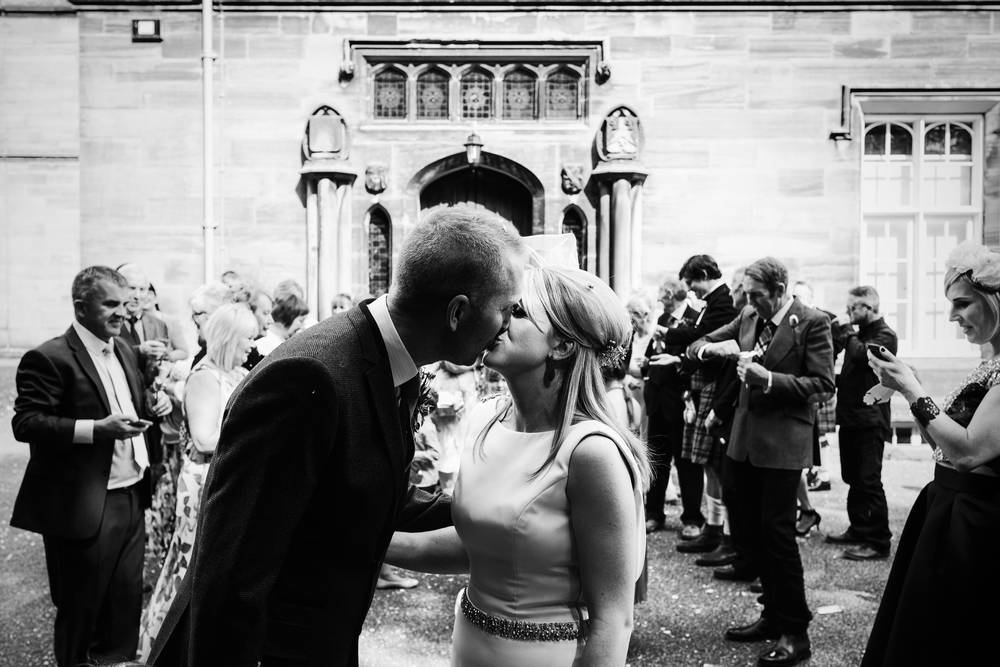 A black and white shot of the bride and groom kissing outside Carlisle Register Office, Cumbria