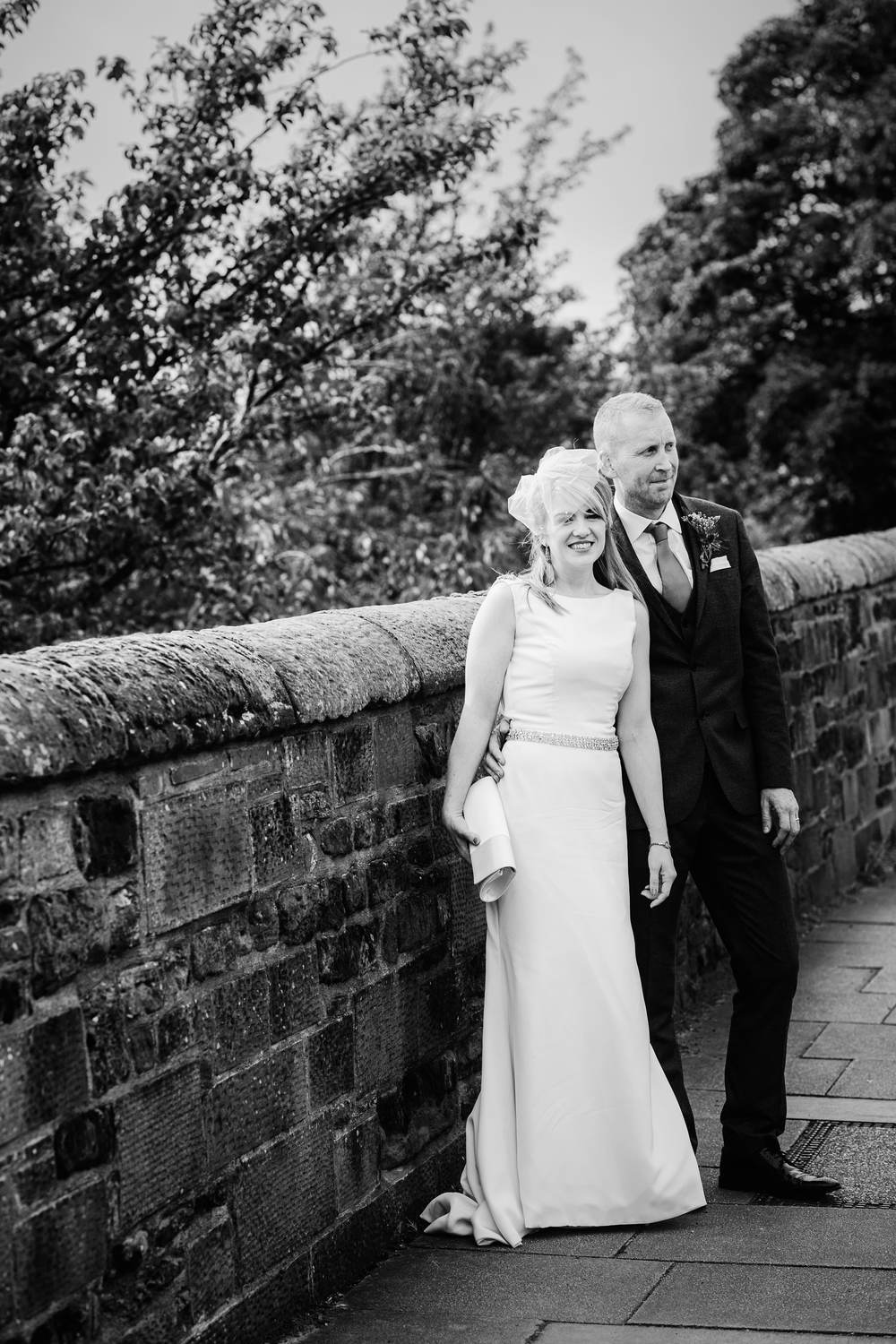 The bride and groom pose beside a wall outside the Tithe Barn, Carlisle, Cumbria in this black and white photograph
