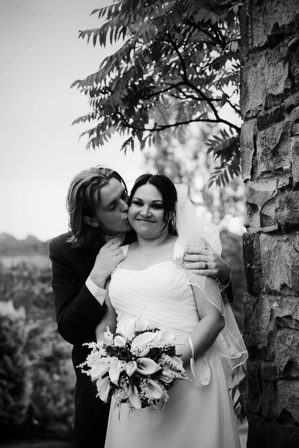 The groom kisses the bride on the neck during black and white photographs taken at South Causey Inn, Durham