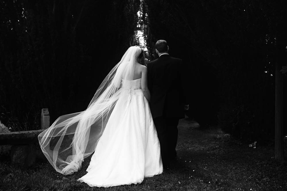 A dramatic black and white photograph of the bride and groom leaving the church at Ellingham Hall, Northumberland