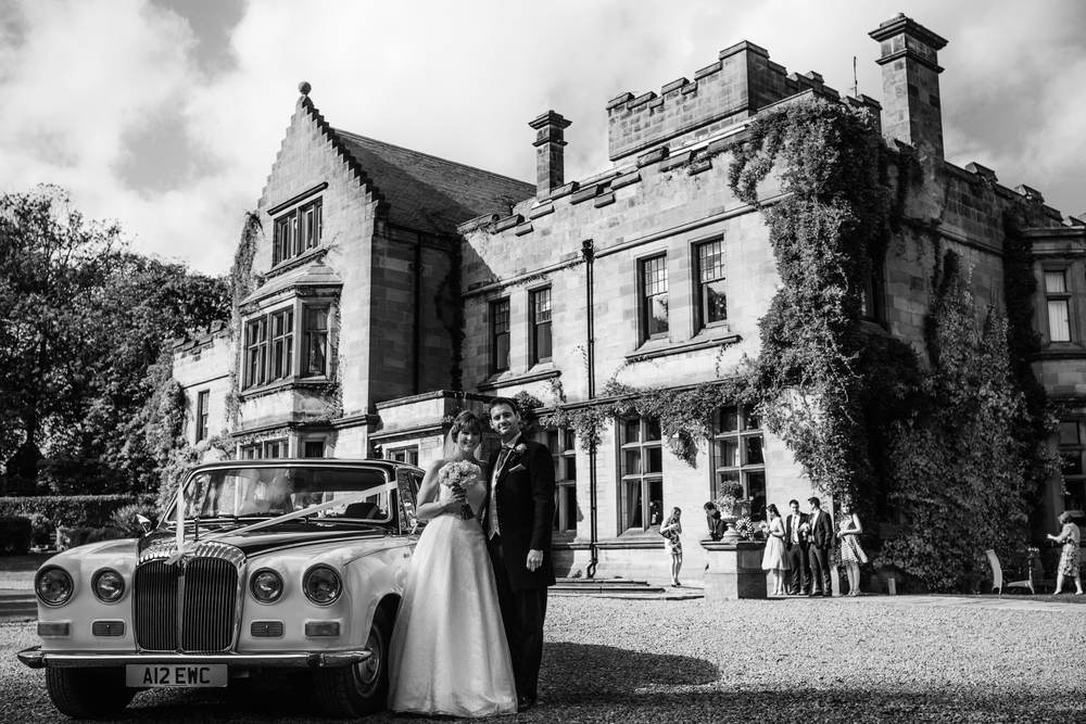 A black and white shot of the bride and groom pose beside their chauffeur driven car outside Ellingham Hall, Northumberland