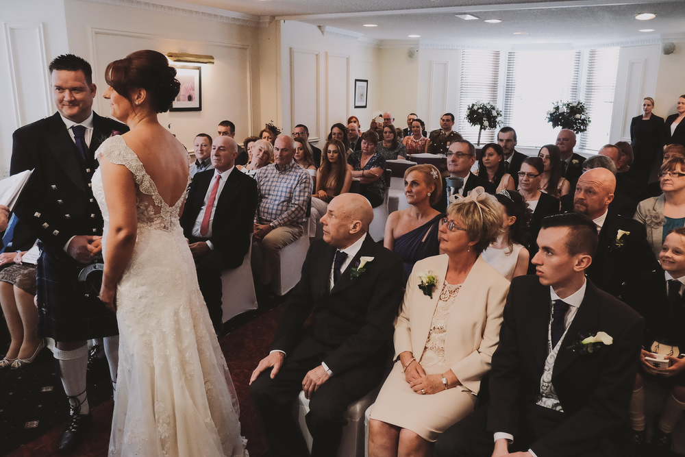Newcastle Wedding Photographer // Bride and Groom during wedding ceremony with family watching