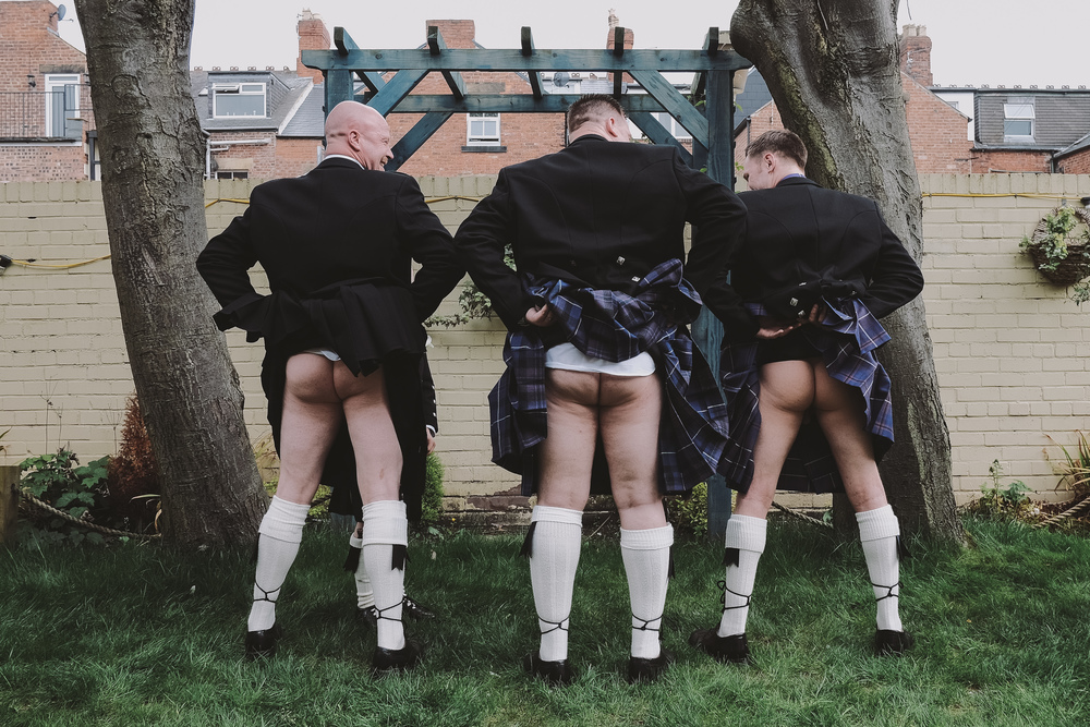 Newcastle Wedding Photographer // Groom and Groomsmen pulling up their kilts