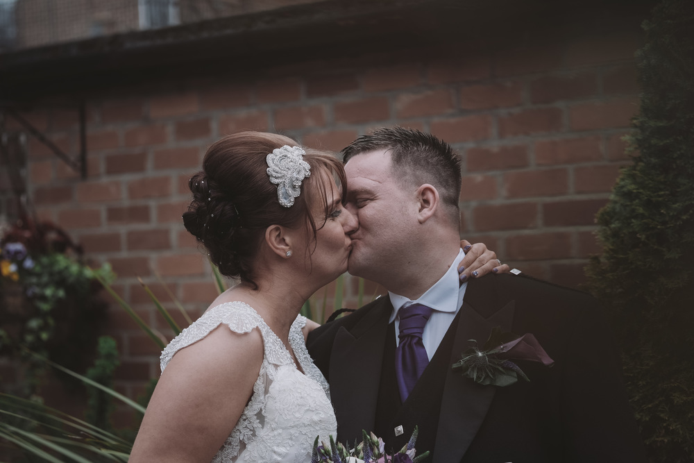 Newcastle Wedding Photographer // Bride and groom kissing in gardens of Caledonian Hotel