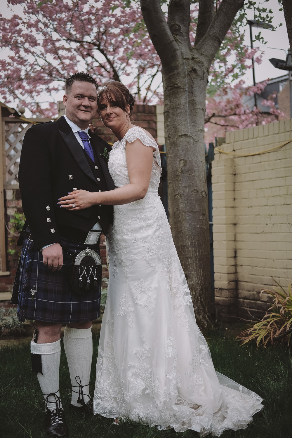 Newcastle Wedding Photographer // Bride and groom pose under blossom tree at Caledonian Hotel