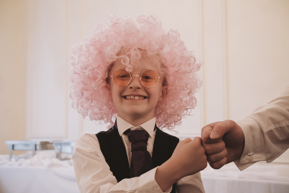 Newcastle Wedding Photographer // Page boy tries on wig at reception