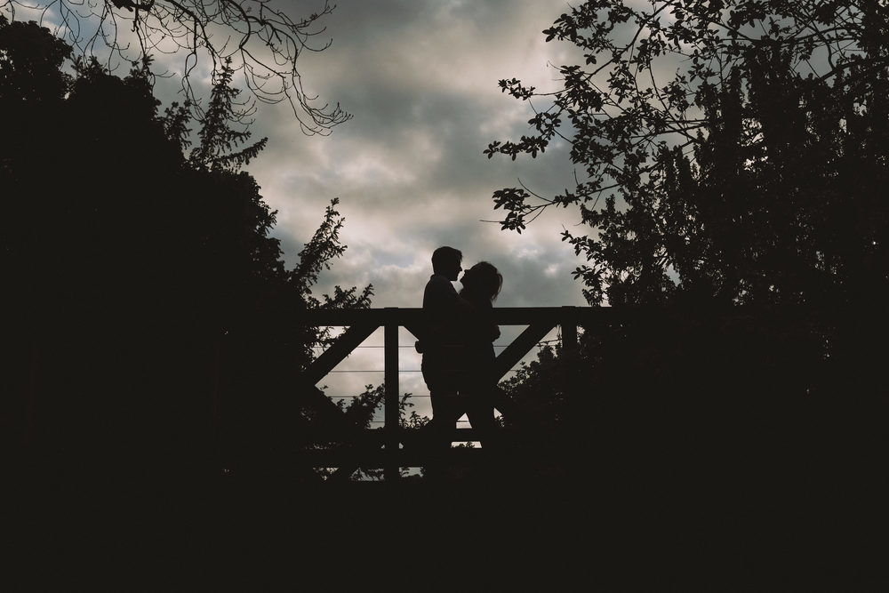 The silhouettes of Ellie & James embrace on a bridge in Saltwell Park, Gateshead, Newcastle upon Tyne