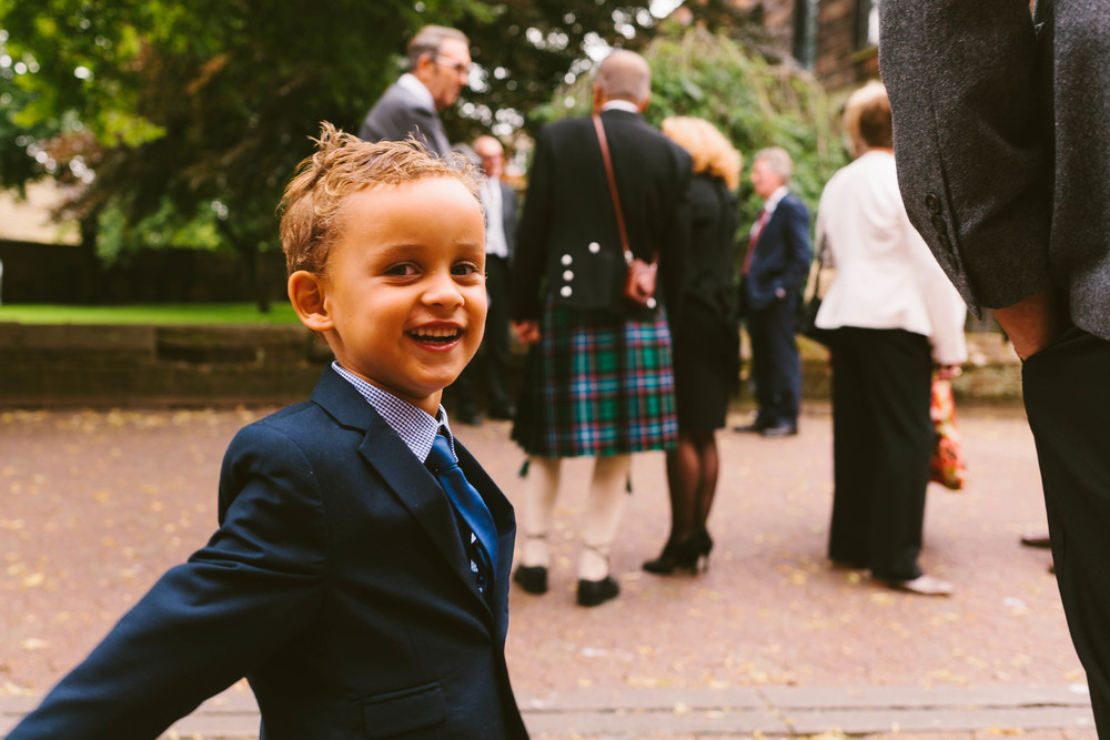 Young smiling boy dressed in suit at a Cumbria wedding photographed by Barry Forshaw