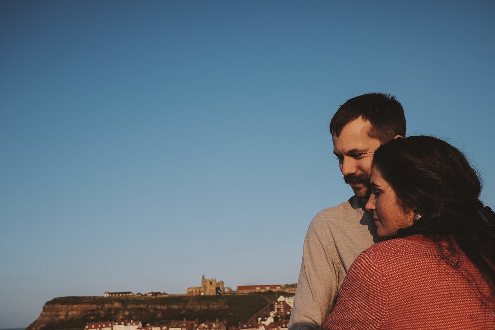 Katy & Tome embrace in an engagement photo by Barry Forshaw, with Whitby Abbey in the background