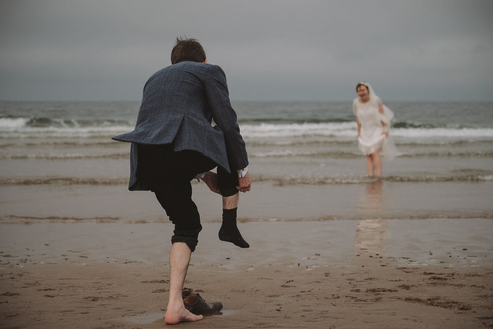 The groom takes off his shoes to join the bride in the sea at a Northumberland wedding by Barry Forshaw