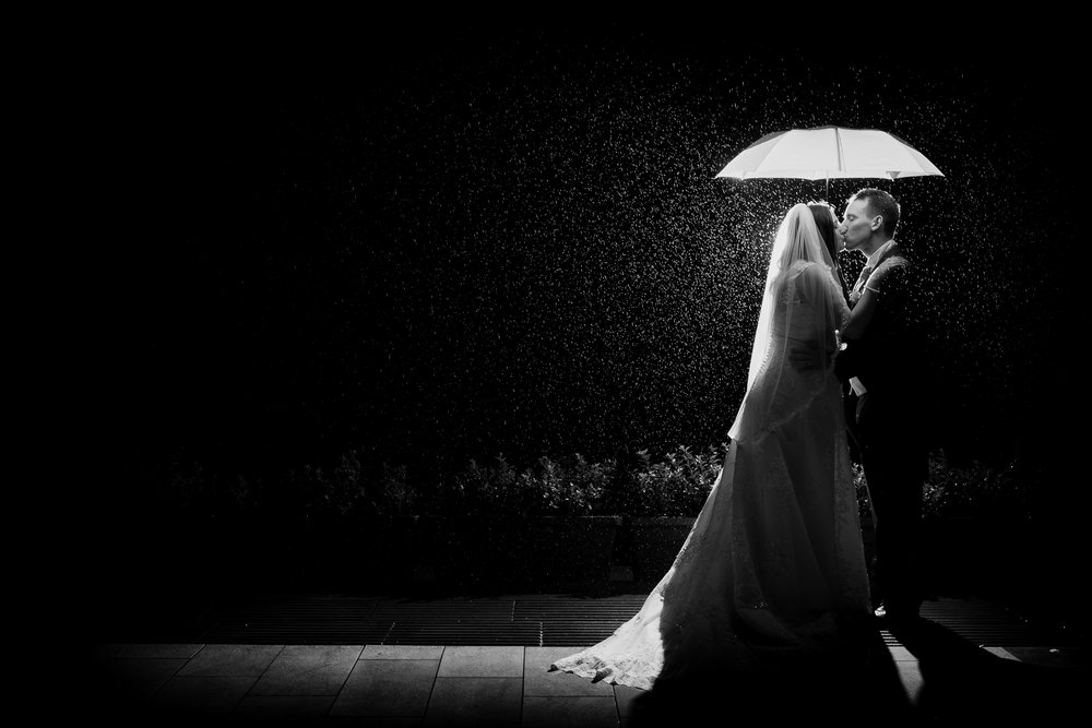 Black and white photo of Kyra & Kev kiss under an umbrella in the rain at Alnwick Garden, Northumberland by Barry Forshaw