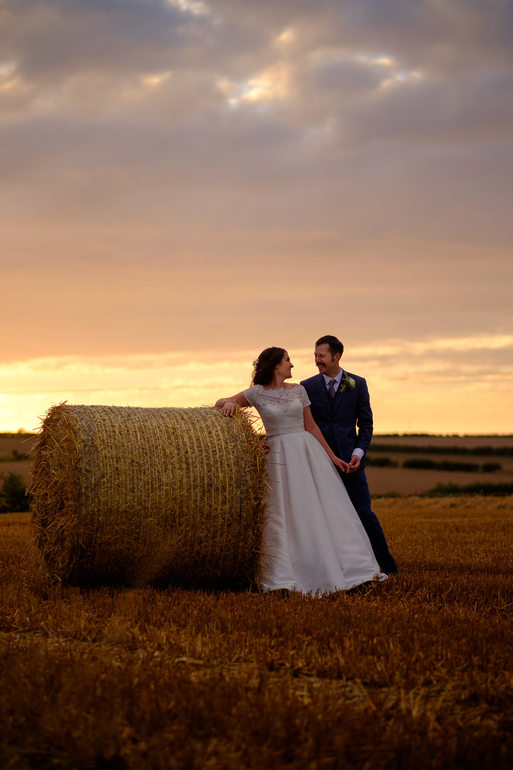 Bride and Groom pose near a hay bale with a spectacular sunset behind on a farm wedding in Yorkshire