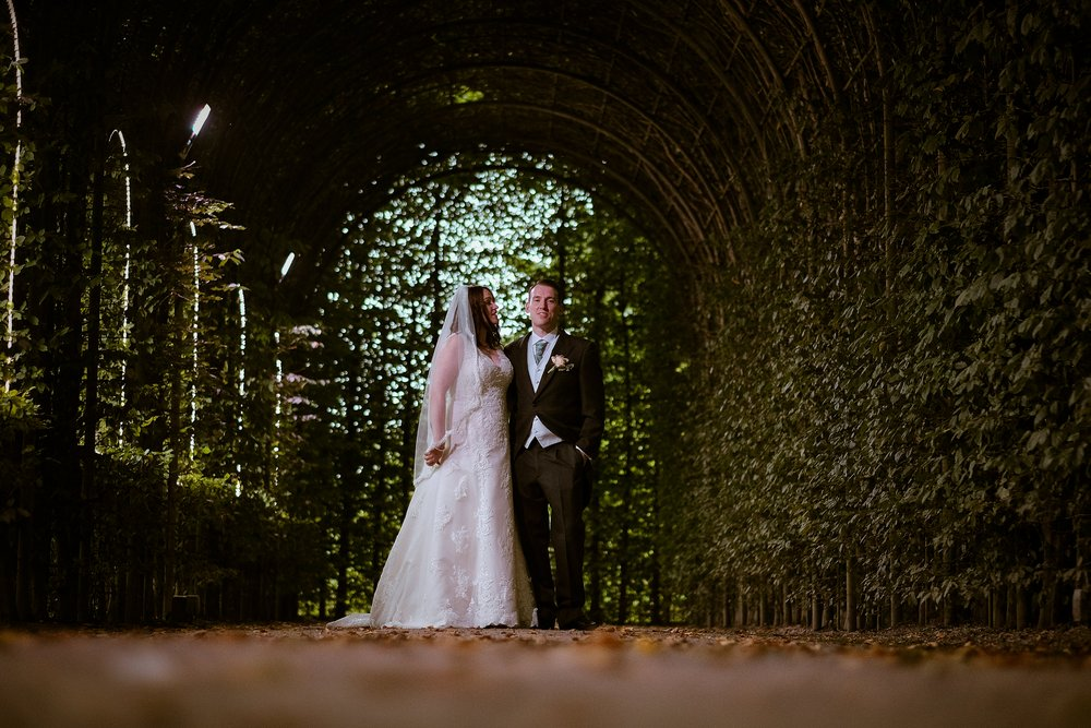 Kyra and Kev under a canopy of leaves at their wedding in The Alnwick Garden Northumberland by Barry Forshaw