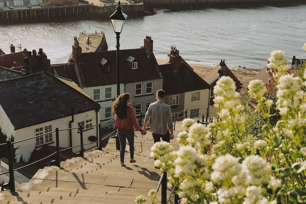 Katy and Tom hold hands while walking down Whitby's 199 steps in Yorkshire on a pre-wedding engagement shoot by Barry Forshaw