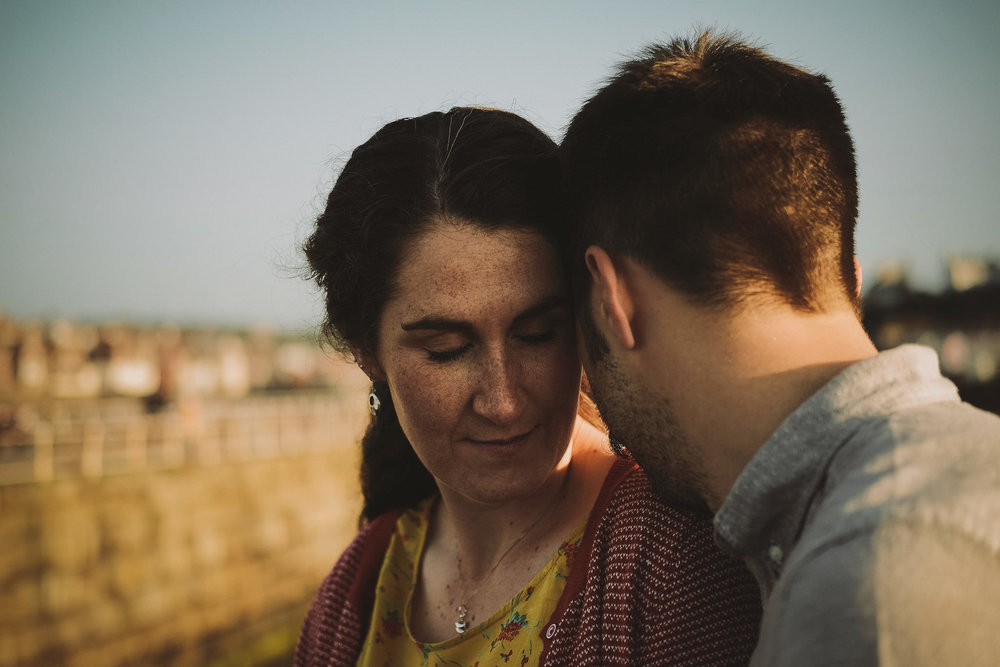 Katy and Tom hold each other close in beautiful light while sitting on Whitby Pier in Yorkshire on a pre-wedding engagement shoot by Barry Forshaw
