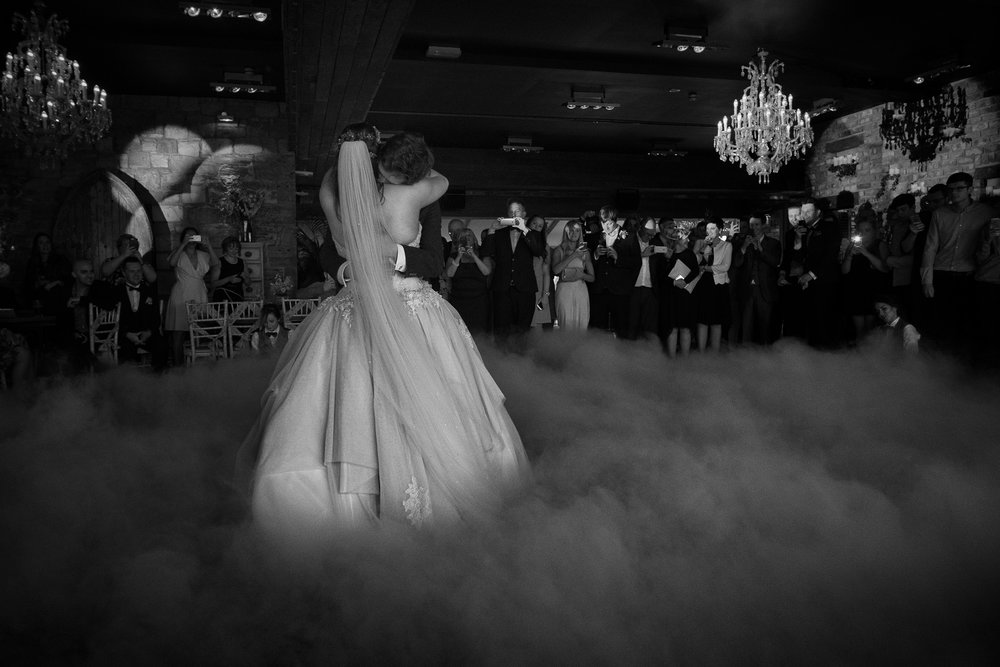 The bride and groom cling onto each other during their first dance as they are wreathed in smoke at Newton Hall Northumberland by Barry Forshaw