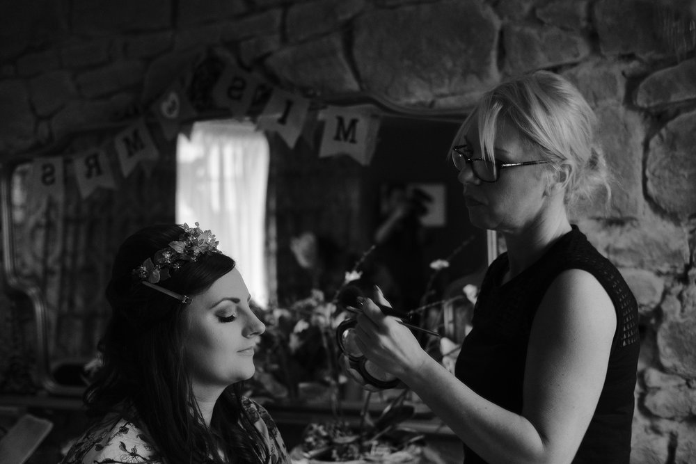 A black and white photograph of Tanya has her bridal makeup applied at Newton Hall, Northumberland by Barry Forshaw