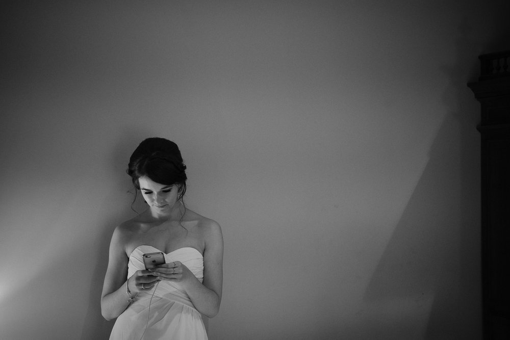 A black and white photo of a bridesmaid checking her telephone during bridal preparations at Newton Hall, Northumberland by Barry Forshaw