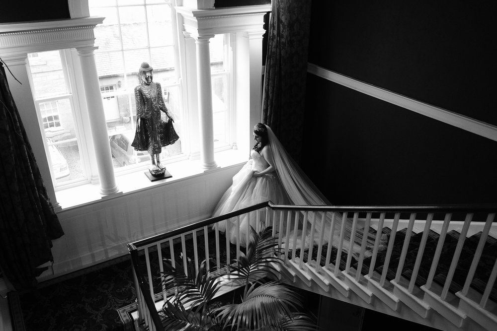A black and white photo of the bride descending the stairs to her wedding at Newton Hall, Northumberland by Barry Forshaw