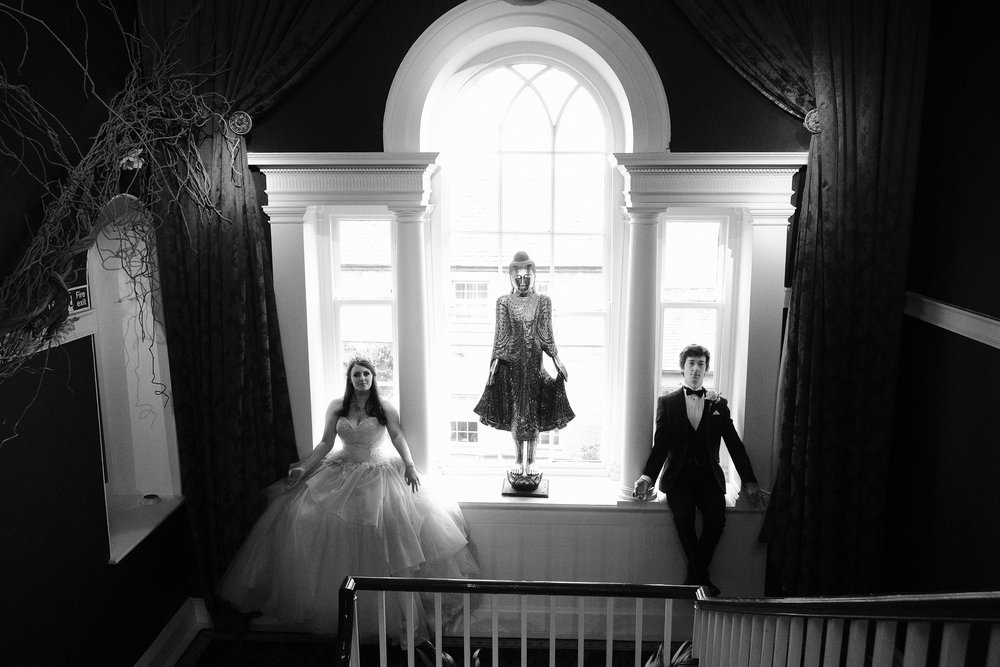 A black and white photo of the bride and groom sitting in a large window tapping their inner spirituality at Newton Hall, Northumberland by Barry Forshaw