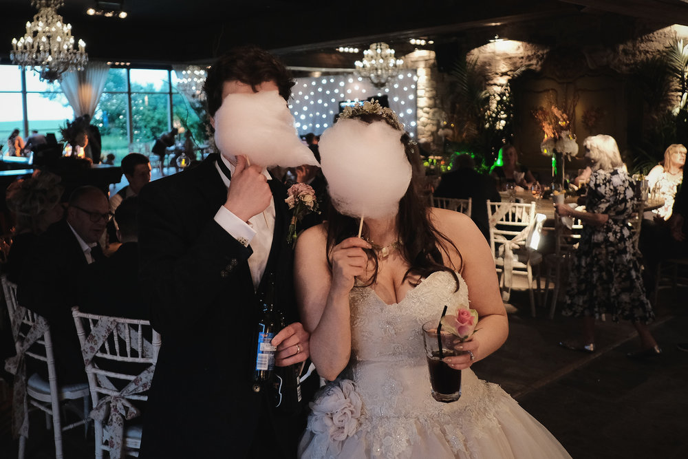 The bride and groom hide behind candy floss at Newton Hall, Northumberland by Barry Forshaw