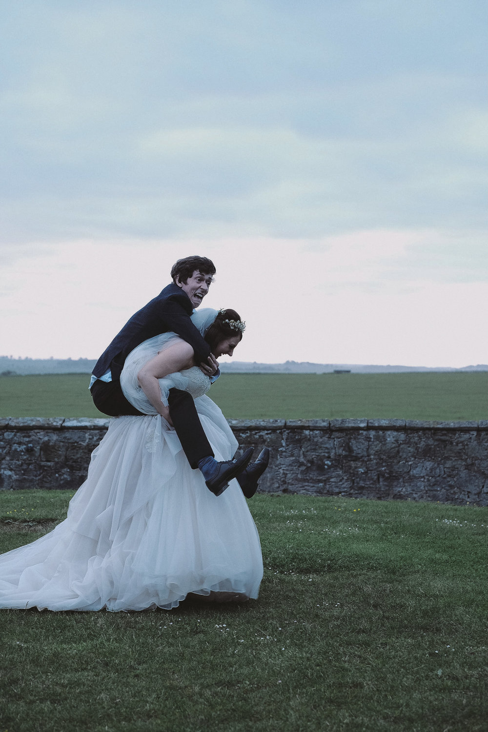 The bride gives the groom a piggy back at Newton Hall Northumberland by Barry Forshaw