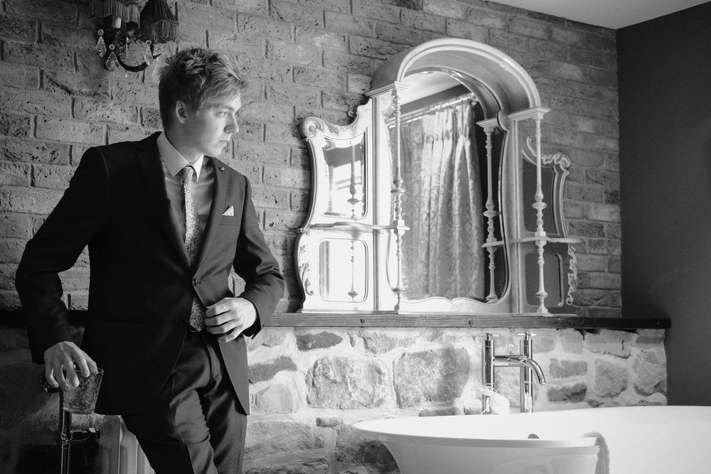 A black and white portrait of a groomsman with a glass of whiskey during groom prep at Newton Hall, Northumberland by Barry Forshaw