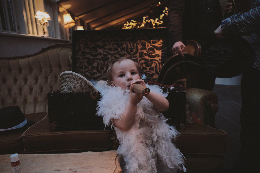 A small child smokes a fake cigar while wearing a feather boa at a wedding at Newton Hall Northumberland by Barry Forshaw