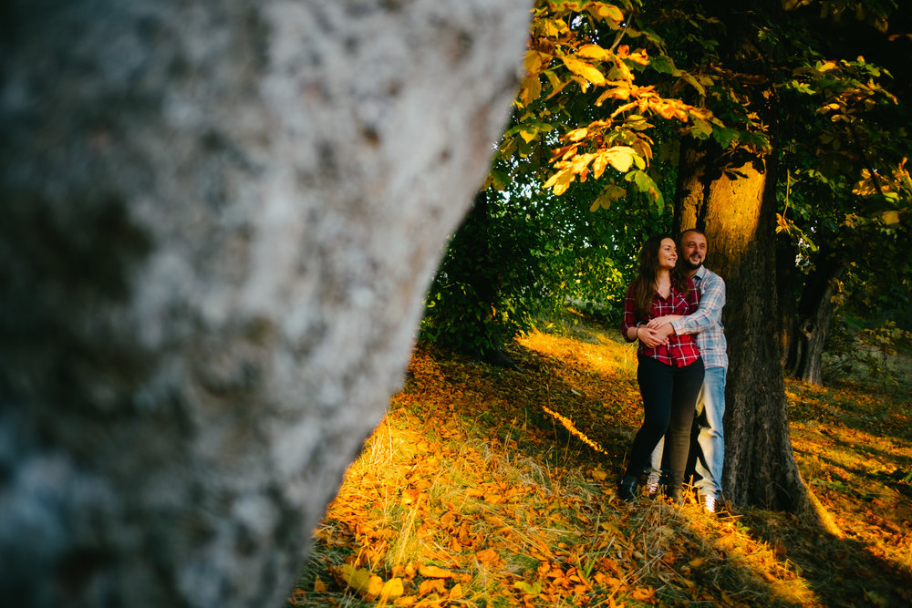 Jen and Joe stand amongst golden leaves under a tree bathed in sunlight at Hylton Castle Sunderland on their pre-wedding photo shoot