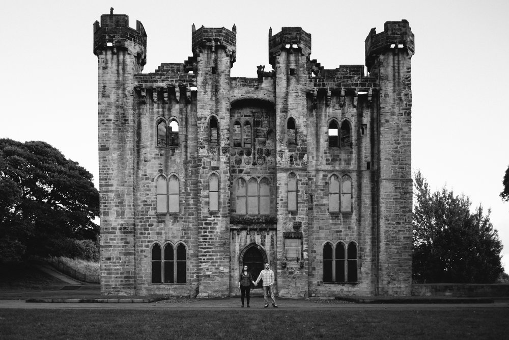 A black and white photo of Jen and Joe standing in front of Hylton Castle Sunderland on their pre-wedding photo shoot