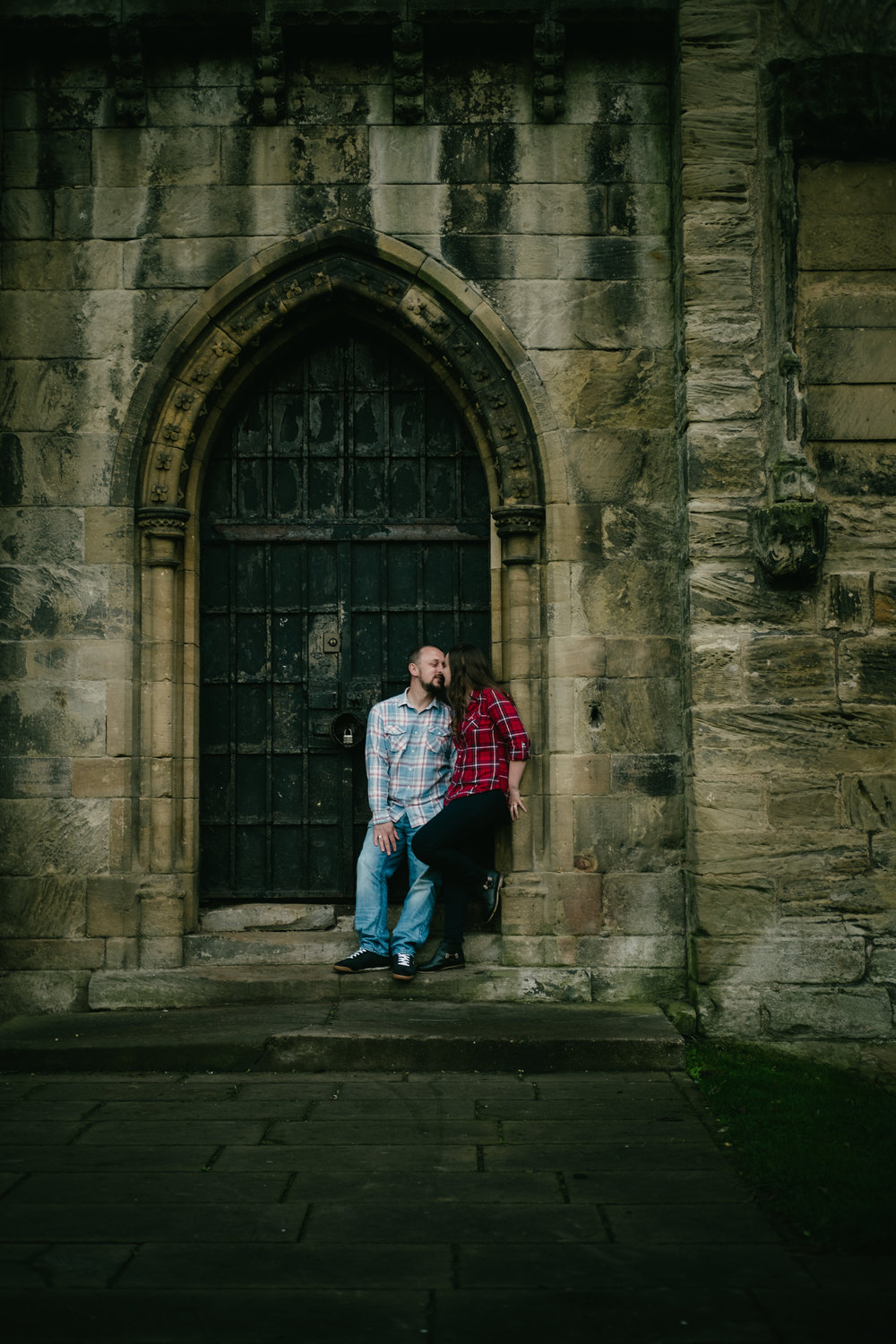 Jen and Joe kiss as they lean against the door of Hylton Castle Sunderland on their pre-wedding photo shoot