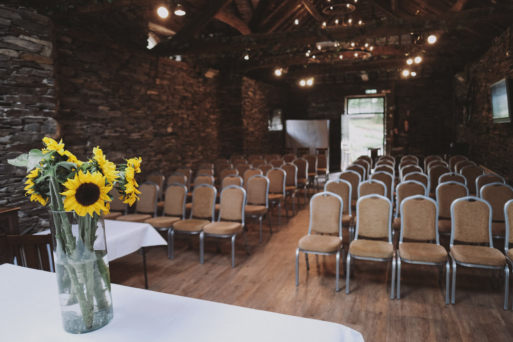 Sunflowers decorate the slate barn at Julia and Darren's Lake District wedding by Barry Forshaw